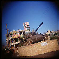 A poster of Hezbollah leader Sayyid Hassan Nasrallah sits with an Israeli tank abandoned in 2000 in the village of Aytaroun, Southern Lebanon, Oct. 23, 2006.