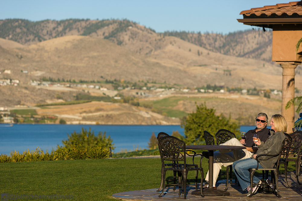 A couple enjoys the view and the wine on the patio at Tsillan Cellars near Chelan, WA.
