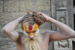 June 28, 2017 - Kathmandu, NP, Nepal - A Hindu Sadhu or Holy Man arrange his long hair at the the premises of Pashupatinath Temple, Kathmandu, Nepal on Wednesday, June 28, 2017. Pashupatinath Temple is listed as a World Heritage Site by UNESCO for its rich culture, temples, and wood, metal and stone artwork. (Credit Image: © Narayan Maharjan/NurPhoto via ZUMA Press)