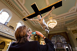 "© Licensed to London News Pictures. 19/02/2015. London, UK. Artist, Nick Reynolds takes a photograph of his lifesize marble crucifixion sculpture of Pete Doherty, called ""For Pete's Sake"", which is unveiled at St. Marylebone Parish Church in London and seen suspended above the aisle of the 200-year-old church. The life-size sculpture was made in 2008 as a collaboration between Pete Doherty and artist, Nick Reynolds. This is the first time the sculpture has been publically displayed and it is part of the exhibition in aid of a fund to help find Tom Moore, who went missing in 2003 called Stations of the Cross, which runs until 17th March and shows other works that make reference to the Passion of Christ. Photo credit : Vickie Flores/LNP"