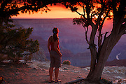 A visitor takes in the sunset at Hopi Point, South Rim, Grand Canyon National Park, Arizona.  (Model Released)