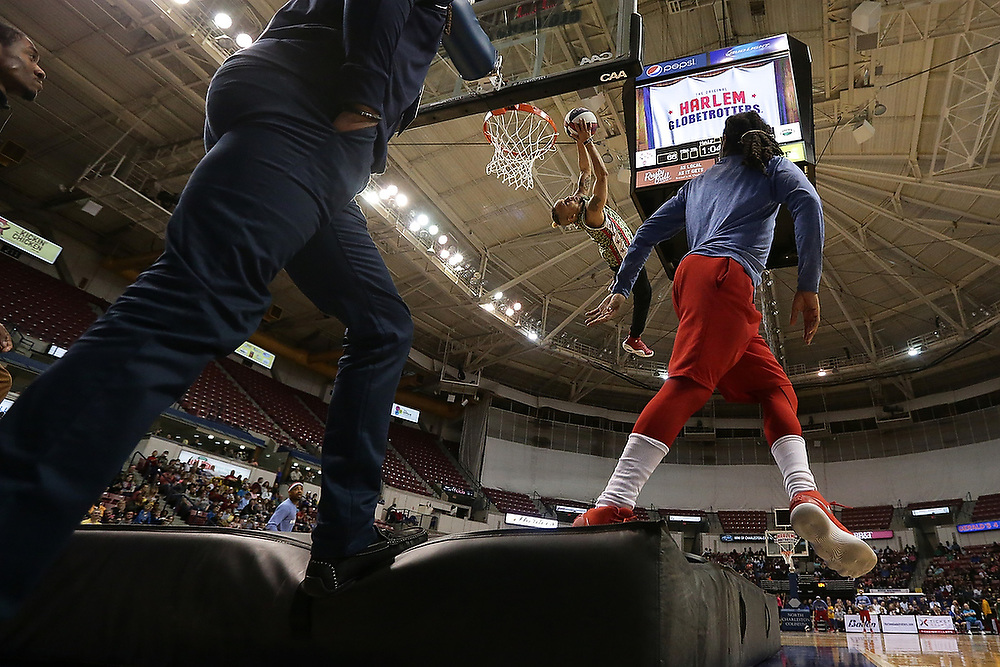 A performer dunks the ball after jumping off of a trampoline during the second half of the game in Charleston. <br /> The Harlem Globetrotters World Tour in Charleston, S.C. on Saturday, March 24, 2018.<br /> Zach Bland Photo