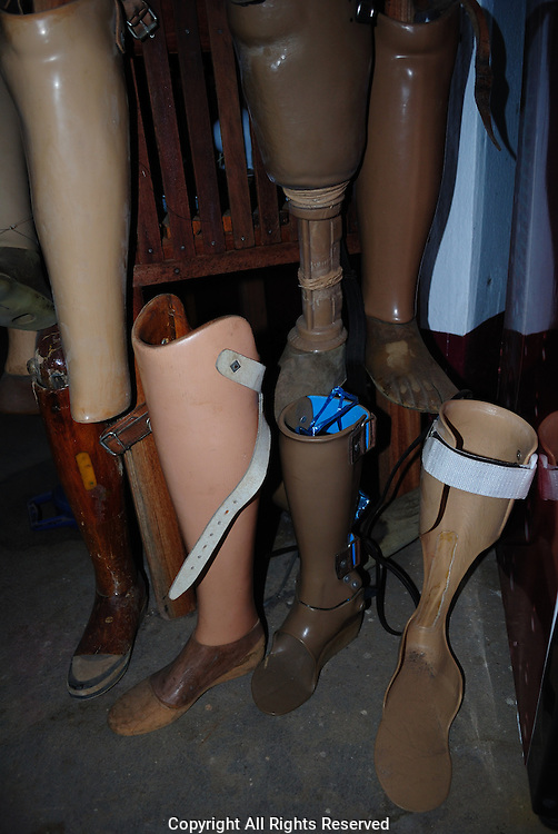 Old artificial limbs at the Mine advisory group (MAG) and Cooperative Orthotic and Prosthetic Enterprise (COPE) project Phonsavan who detail the effects and fight against unexploded ordnance.