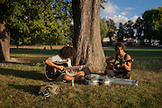 Two musincians practice their songs in late afternoon sunshine in Ruskin Park, south London borough of Southwark, England UK.