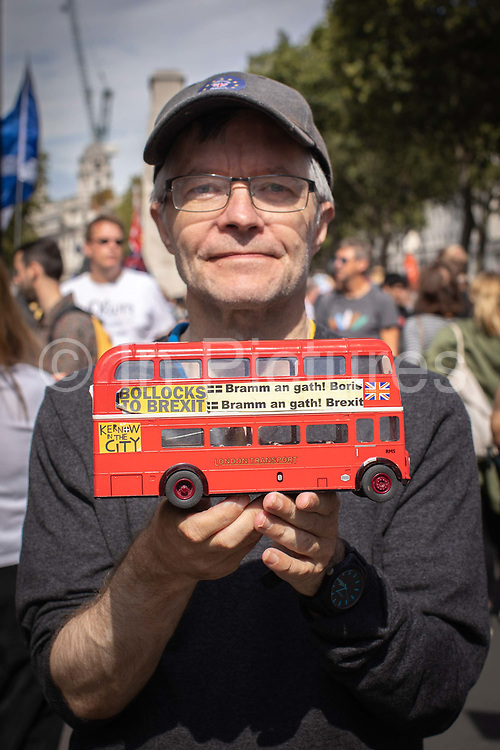 A male protester from Cornwall holding a toy London bus during the Stop The Coup protest against the proroguing of Parliament on 31st August 2019 in London in the United Kingdom. Left-wing group Momentum and the Peoples Assembly coordinated a series of Stop The Coup protests across the UK today, aimed at Boris Johnson and the UK government proroguing Parliament.