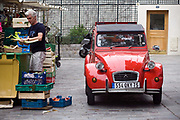 A man cleans vegetables behind a market stall next to a typically French car on the Rue Mouffetard.<br /> Rue Mouffetard is in the Fifth (cinquieme) arrondisement and the street is very old: originally a Roman rod running from the Roman Rive Gauche city south the Italy. The market is famous for it's quality fresh produce and artisanal food shops.
