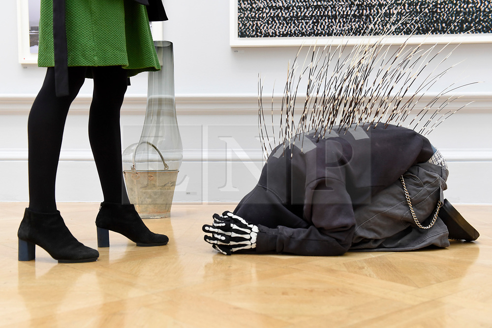 """© Licensed to London News Pictures. 08/06/2017. London, UK. A visitor views a sculpture called """"The Art of Being Right"""" by Lee Wagstaff (GBP12,000).  Preview of the Summer Exhibition 2017 at the Royal Academy of Arts in Piccadilly.  Co-ordinated by Royal Academician Eileen Cooper, the 249th Summer Exhibition is the world's largest open submission exhibition with around 1,100 works on display by high profile and up and coming artists.<br />  Photo credit : Stephen Chung/LNP"""