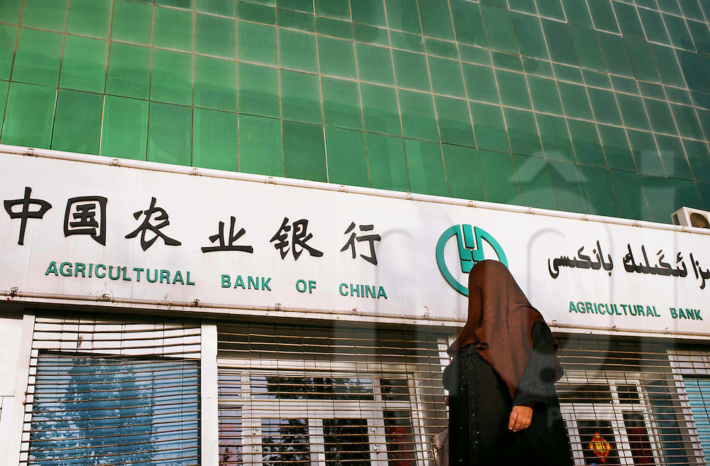 A veiled Uyghur woman walks in front of a bank, Kashgar, China, Asia
