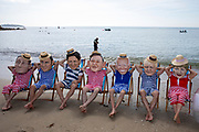 A giant message in a bottle has washed up on the beach from countries ravaged by climate change, but the G7 leaders are too busy relaxing in their swimming costumes in deckchairs to notice, Oxfam campaigners pose as G7 leaders on a beach on the 12th of June 2021 near Falmouth, Cornwall, United Kingdom. Oxfam is calling on the G7 countries to commit to cutting emissions further and faster and provide more finance to help the most vulnerable countries respond to the impacts of climate change.(photo by Andrew Aitchison/In Pictures via Getty Images)