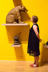 © Licensed to London News Pictures. 08/06/2014. London, UK. A woman looks at a bear at the British Folk Art exhibition at Tate Britain in Millbank, London on 8th June 2014. The British Folk Art exhibition at Tate Britain opens on 10th June 2014 and runs until 31st August 2014. Photo credit : Vickie Flores/LNP