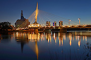 Canadian Museum for Human Rights (CMHR) and the Esplanade Riel Bridge and the Red River at dusk<br /> Winnipeg<br /> Manitoba<br /> Canada