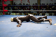 Skeleton wrestler on floor of ring. Lucha Libre wrestling origniated in Mexico, but is popular in other latin Amercian countries, including in La Paz / El Alto, Bolivia. Male and female fighters participate in the theatrical staged fights to an adoring crowd of locals and foreigners alike.