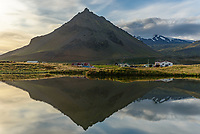 The pyramid shaped Stapafell is reflected in a calm pond in Arnarstapi, Iceland.