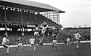 Two players jump high competing to gain possession of the ball as their team mates watch during the All Ireland Minor Gaelic Football Final, Tyrone v Kerry in Croke Park on the 28th September 1975.