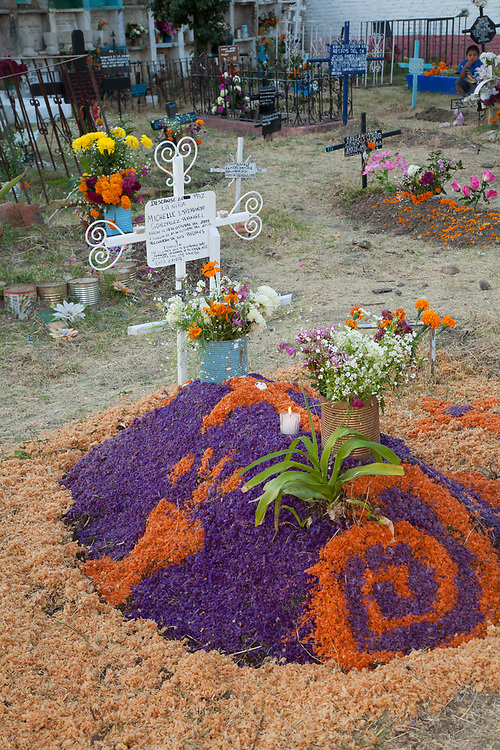 North America, Mexico, San Miguel de Allende, grave in cemetery decorated with flower petals and flowers during Day of the Dead  celebration, also known as Dios de los Muertos.  Mexicans celebrate the Day of the Dead on November 1st and 2nd in connection with the Catholic holy days of All Saints' Day and All Souls' Day.