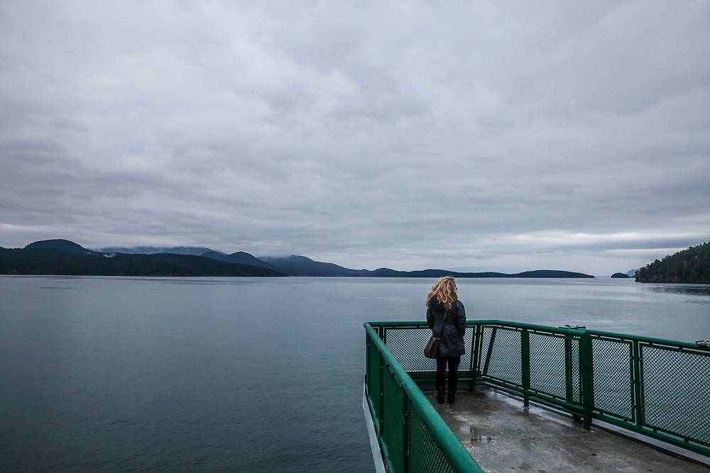 A woman stands on the observation deck on a Washington State Ferry as it sails through the San Juan Island, Washington State, USA.