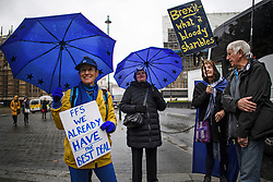 © Licensed to London News Pictures. 21/10/2019. London, UK. Anti-Brexit protestors shelter from the rain underneath Umbrella, outside the Houses of Parliament in Westminster, London. Last week Parliament sat on a Saturday for the first time since 1982, but failed to vote on Boris Johnson's new Brexit deal. Photo credit: Ben Cawthra/LNP
