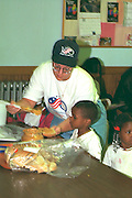 Volunteer fixing lunch for kids Sharing & Caring Hands soup kitchen.  Minneapolis Minnesota USA