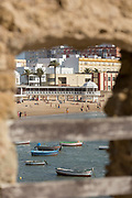 Beach with tourists seen through old window, Cadiz, Andalusia, Spain