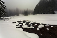 River in the snow in misty mountain