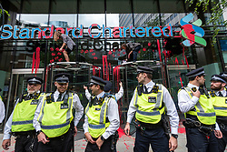 """© Licensed to London News Pictures. 27/08/2021. LONDON, UK.  Police in front of climate activists from Extinction Rebellion daubing fake blood on the entrance of Standard Chartered Bank during a protest in The City of London.  The event is part of the 'Impossible Rebellion' protest to """"target the root cause of the climate and ecological crisis"""" and are ongoing for two weeks until the Government agrees to stop all new fossil fuel investments.  Photo credit: Stephen Chung/LNP"""