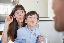 Mother and son having fun with spaghetty