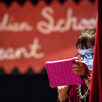 The glow of a mobile tablet illuminates the face of Mia Autumn Baca as she performs a piano song during the 2018 Saint Michael Indian School Princess Pageant in St. Michael Thursday.