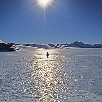 A hiker crosses a bare ice glacier below the Patriot Hills in the southern Ellsworth Mountains, Antarctica.  This glacier, polished by katabatic winds, is the ongoing site of the first-ever wheeled aircraft landings on the continent.