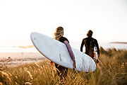 Couple with surfboards walking through the long grass in the sand dunes, ready to go surfing at St Ouen's Bay, Jersey, CI