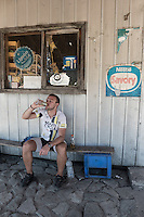 Cyclist drinking energy drink outside a small shop in Villa Santa Lucia, a small village located by the Carretera Austral, Chile