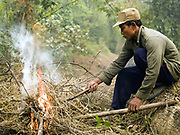 A Khmu ethnic minority man lights a fire to burn the dry vegetation on his upland field, Ban Non Boun Kang, Phongsaly province, Lao PDR. Swidden cultivation or 'hai' in Lao consists of cutting the natural vegetation, leaving it to dry and then burning it for temporary cropping of the land, the ash acting as a natural fertiliser. Shifting cultivation practices, although remarkably sustainable and adapted to their environment in the past, have come under increasing stress in recent decades and are now starting to be a major problem in Lao PDR, causing widespread deforestation and watershed degradation.