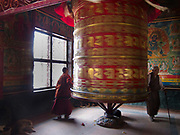 Two buddhists walk around and spin a gigantic prayer wheel according to their religion in a temple next to the Boudhanath stupa, a world heritage site and a very important place for Buhddist pilgrimage near Kathmandu.