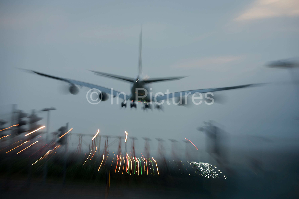 A burred jet airliner lands at London Heathrow airport, coming in over the perimeter fence on the southern runway. As the plane descends, we see its blurred shape against the dusk sky - a busy time in the airport's day. London Heathrow is a major international airport, the busiest airport in the United Kingdom and the busiest airport in Europe by passenger traffic. It is also the third busiest airport in the world by total passenger traffic, handling more international passengers than any other airport around the globe. From the chapter entitled 'Up in the Air' and from the book 'Risk Wise: Nine Everyday Adventures' by Polly Morland (Allianz, The School of Life, Profile Books, 2015).