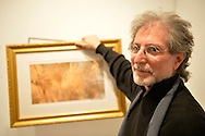 Huntington, New York, U.S. - March 1, 2014 -  Artist BARRY FEUERSTEIN holds one of his golden framed images at the Opening Reception '3 Wild & Crazy Artists' at FotoFoto Gallery, where he exhibited 'Red & White Paintings & Photographs – El Vocio Existential.'