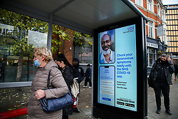 © Licensed to London News Pictures. 30/10/2020. London, UK. A woman wearing a face covering waiting at a bus stop next to a NHS COVID-19 App poster in north London. Pressure is mounting on the Prime Minister Boris Johnson and Ministers to impose a second national lockdown and London is likely to go into Tier 3 in the coming weeks as coronavirus cases are increasing. Photo credit: Dinendra Haria/LNP
