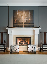 Fireplace with white wood mantel with fire and two modern ottomans