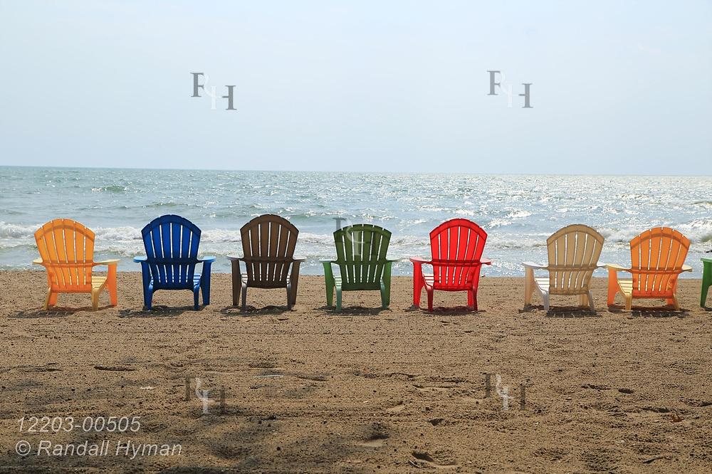 Colorful Adirondack chairs line Lake Huron beach at Riptide Inn in East Tawas, Michigan.