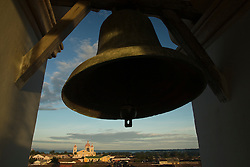 Central America, Nicaragua, Granada.  Giant bell in belltower of Iglesia La Merced (La Merced Church) with Cathedral of Granada and Lake Cocibolca (Lake Nicaragua) in distance.