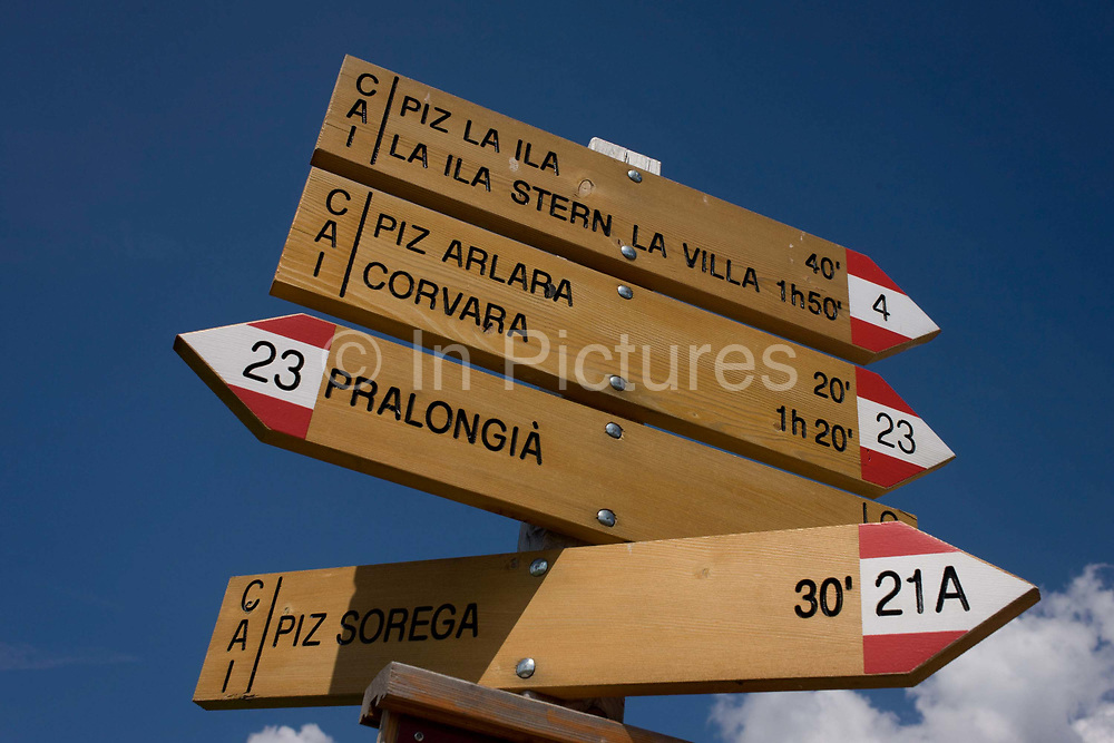 Hiking trail route signpost in the Pralongià above San Cassiano-St. Kassian in the Dolomites, south Tyrol, northern Italy. In winter, the Pralongià meadows are the heart of Alta Badia's skiing area. Hiking trails lead across the high alpine pastureland between Corvara and San Cassiano (St. Kassian) with hilly upland meadows with vast mountain pastures and many old hay huts, a pretty group of trees at the edges of the meadows, and the beautiful shapes of the surrounding mountains, which include the Gruppo di Sella (Sellastock) Massif, Sassongher, Monte Cavallo (Heiligkreuzkofel), Cunturines and Lagazuoi.