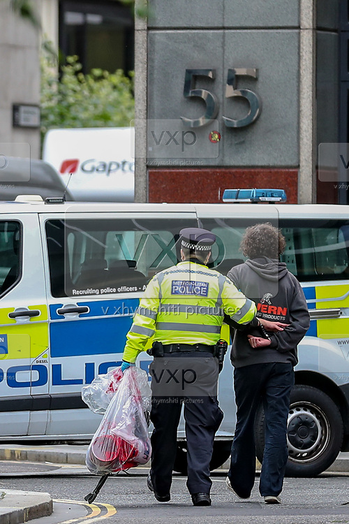 Police arrested two Extinction Rebellion activists who threw red paint at the entry doors of Standard Chartered bank during a march protest organised by environmental activist group in London on Friday, Aug 27, 2021. XR are planning to hold multiple actions over two weeks from August 23rd 2021 aiming to disrupt the City of London and further afield and put climate change at the top of the agenda ahead of the UK hosting COP26 Summit later this year. (VX Photo/ Vudi Xhymshiti)