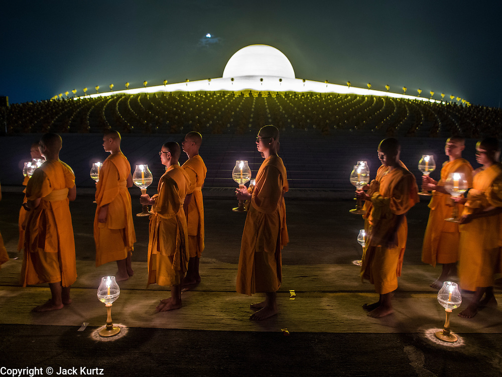 """14 FEBRUARY 2014 - KHLONG LUANG, PATHUM THANI, THAILAND: Buddhist monks participate in the evening candle light procession for Makha Bucha Day at Wat Phra Dhammakaya. The aims of Makha Bucha Day are: not to commit any kind of sins, do only good and purify one's mind. It is a public holiday in Cambodia, Laos, Myanmar and Thailand. Many people go to the temple to perform merit-making activities on Makha Bucha Day. The day marks four important events in Buddhism, which happened nine months after the Enlightenment of the Buddha in northern India; 1,250 disciples came to see the Buddha that evening without being summoned, all of them were Arhantas, Enlightened Ones, and all were ordained by the Buddha himself. The Buddha gave those Arhantas the principles of Buddhism, called """"The ovadhapatimokha"""". Those principles are:  1) To cease from all evil, 2) To do what is good, 3) To cleanse one's mind. The Buddha delivered an important sermon on that day which laid down the principles of the Buddhist teachings. In Thailand, this teaching has been dubbed the """"Heart of Buddhism."""" Wat Phra Dhammakaya is the center of the Dhammakaya Movement, a Buddhist sect founded in the 1970s and led by Phra Dhammachayo.    PHOTO BY JACK KURTZ"""