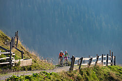 Two mountain bikers riding on dirt road on hill with mountain in background, Zillertal, Tyrol, Austria