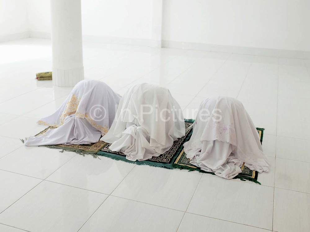 Muslim Cham women praying in the women's prayer room at the mosque in Van Lam village, Ninh Thuan province, Central Vietnam. The Cham people are remnants of the Kingdom of Champa (7th to 18th centuries) and are recognised by the government as one of Vietnam's 54 ethnic groups. The majority of Cham in Vietnam (also known as the Eastern Cham) are Hindu but there is also a sizeable Muslim community of around 39,000 people inhabiting Ninh Thuan and Binh Thuan provinces along the coast of central Vietnam.
