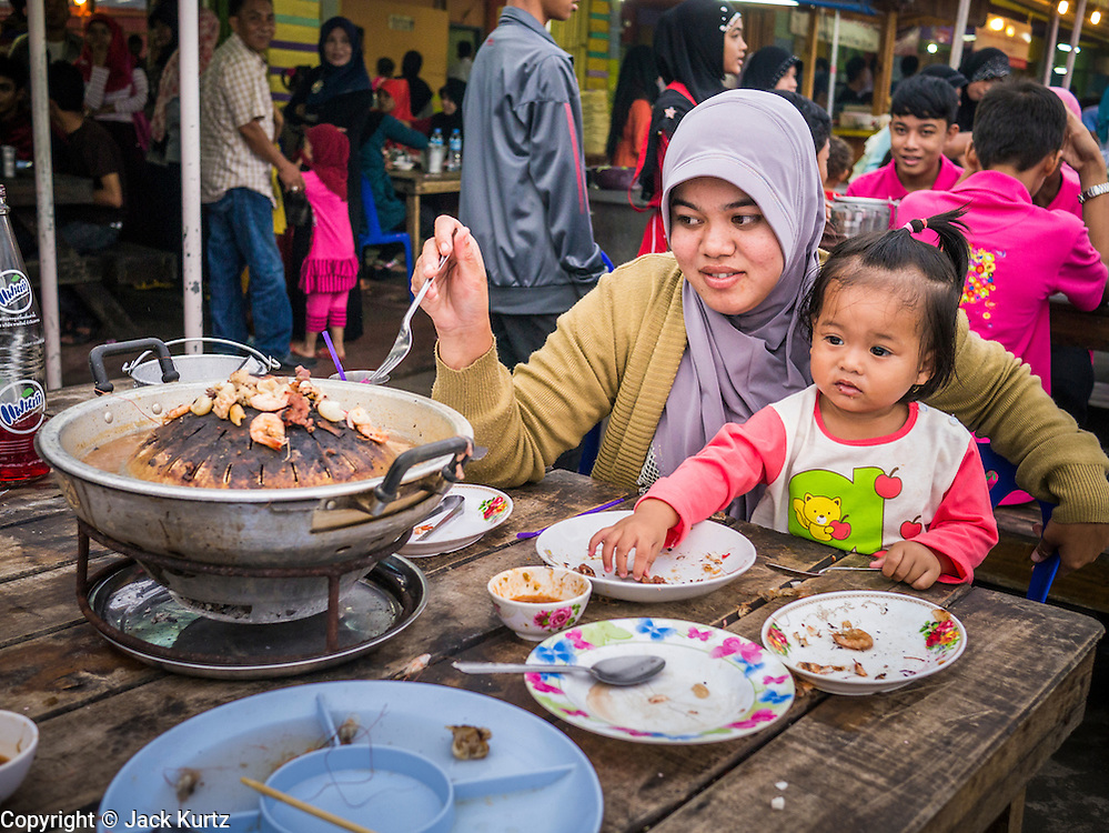 08 JULY 2013 - PATTANI, PATTANI, THAILAND:   A Thai Muslim woman and her daughter at a seafood barbecue restaurant in Pattani, Thailand, Monday, the day before Ramadan. Ramadan starts July 9 and Monday was the last day observant Muslims were able to eat and drink during daylight hours. Muslims fast during the holy month of Ramadan, taking breakfast before dawn and not eating again until after sunset. The restaurants in Pattani, a Muslim majority city in southern Thailand, were packed Monday afternoon and evening.  PHOTO BY JACK KURTZ