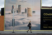 A woman walks beneath a property developer's billboard showing a large aerial image of London skyscrapers in low cloud. Carrying a coffe in one hand, the lady walks northwards up Shoreditch High Street. This site will be called Principal Place, a new 15-storey office block designed by Foster and Partners in Worship Street, Shoreditch, London. The mural image shows some of the capital's best-known tall buildings that rise above the fog - now a very unusual weather phenomenon after thick fogs in the 1950s.