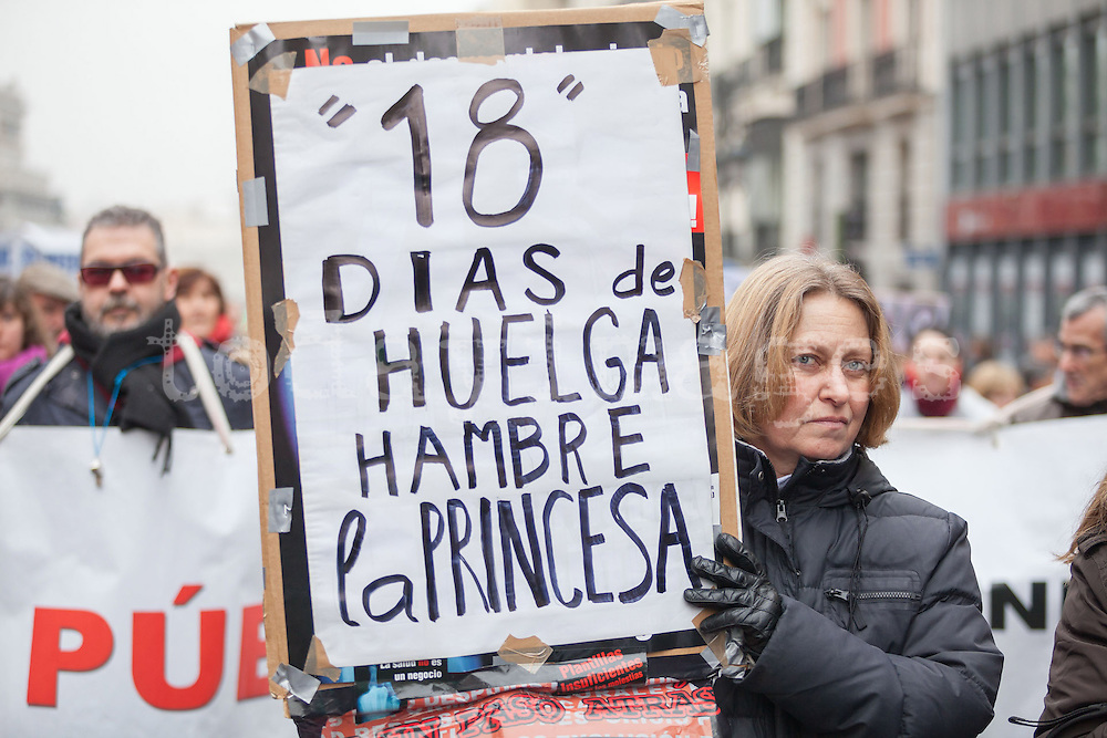 During the fist Spanish protest of 2013  against health privatization, a woman is holding  a placard for Juan Recio on hunger strike 18 days