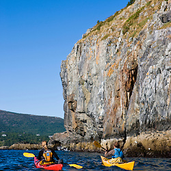 A man and woman sea kayaking near Bald Porcupine Island in Maine's Acadia National Park.  Bar Harbor.