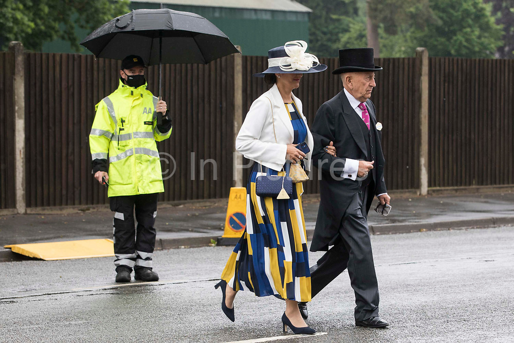 Racegoers arrive on Ladies Day at Royal Ascot on 17th June 2021 in Ascot, United Kingdom. Despite Covid restrictions and changeable weather including some rain, many racegoers displayed the elaborate hats and fascinators for which Gold Cup Day has become well known.
