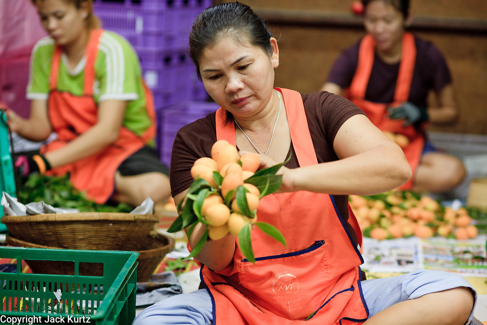 "Mar. 9, 2009 -- BANGKOK, THAILAND: Women package and sort fruit in the flower and produce market on the Chao Phraya River in Bangkok. Every morning, flowers and produce from the provinces arrive in the market where they are bundled and sold at retail in Bangkok's consumer markets. Many of the flowers are sold in and around the Buddhist temples in Bangkok. People buy them as offerings or to ""make merit."" Photo by Jack Kurtz / ZUMA Press"