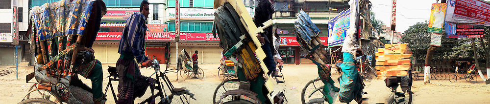 DHAKARAMA by Enamul Hoque<br /> <br /> Dhakarama is a photographic exhibition of street panoramas of Dhaka by London<br /> based photographer Enamul Hoque. <br /> <br /> Hoque regularly visits Dhaka and continues<br /> to experiment and push the boundaries of digital technology in archiving and creating an intimate portrait of an evolving megacity.<br /> <br /> Dhaka is the capital of Bangladesh and is one of the most densely populated megacities in the world, with a population of over 17 million people. <br /> <br /> The images are of some of the main streets of Dhaka, and reflect the colour, vitality, chaos and<br /> life in a densely packed city.<br /> <br /> These photographs were taken 2013 onwards and reflect his continual interest in representation the daily life and form part of his work as a visual artist.<br /> <br /> It contrasts the structured / controlled work that he is regularly involved in and provides an<br /> insight into the way photography can be used to represent motion.